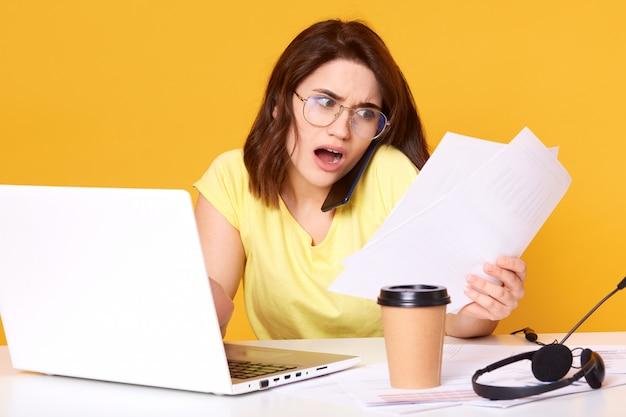 黄色で分離されたオフィスで紙の文書を扱う、レポートをチェックし、多くの間違いを見つける緊張の若いブルネットビジネス女性は、驚きの表情を見せています。