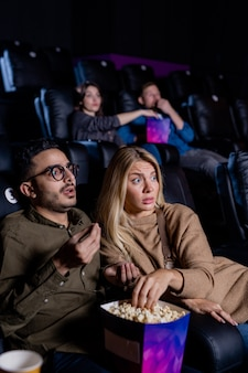 Tense young couple with box of popcorn watching action movie while sitting in dark cinema in front of screen