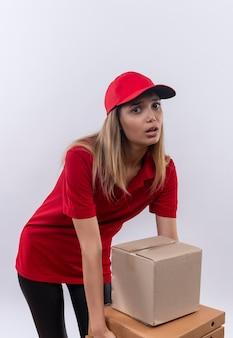 赤の制服とキャップを身に着けている緊張した若い配達の女の子は、白で隔離された多くの箱を保持しようとしています
