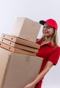 Tesa giovane ragazza di consegna che indossa l'uniforme rossa e il cappuccio che tiene molte scatole isolate su bianco