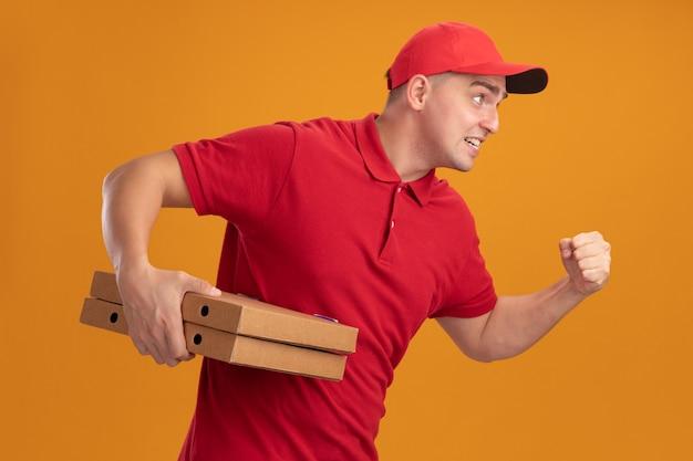 オレンジ色の壁に分離された実行中のジェスチャーを示すピザの箱を保持しているキャップと制服を着た緊張した若い配達人