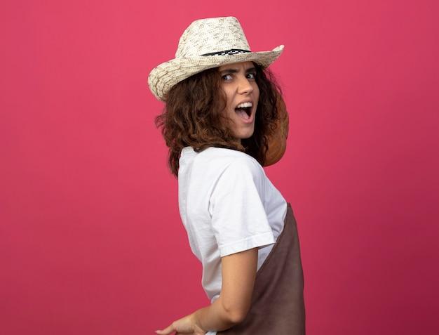 カボチャを肩に置くガーデニング帽子をかぶった制服を着た緊張した若い女性の庭師