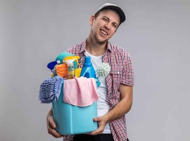 白い壁に分離されたクリーニングツールとバケツを保持しているキャップを身に着けている緊張した若い男クリーナー
