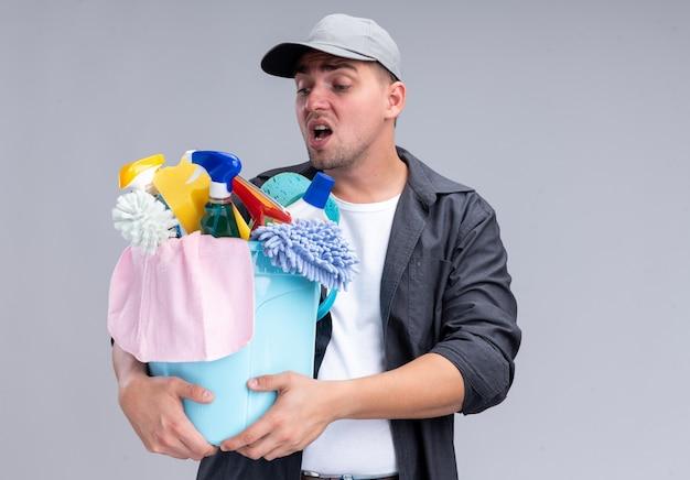 Напряженный молодой красивый уборщик в футболке и кепке держит и смотрит на ведро с чистящими средствами, изолированное на белой стене