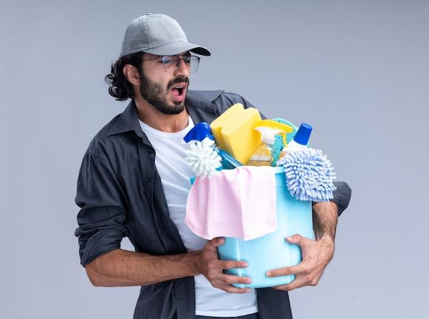 Напряженный молодой красивый уборщик в футболке и кепке держит ведро с чистящими средствами, изолированное на белой стене