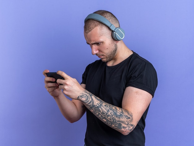 Tense young handsome guy wearing black t-shirt with headphones playing on phone isolated on blue wall