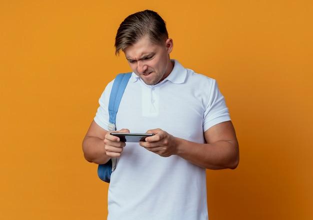 オレンジ色に分離された電話で遊んだバックバッグを身に着けている緊張した若いハンサムな男性学生