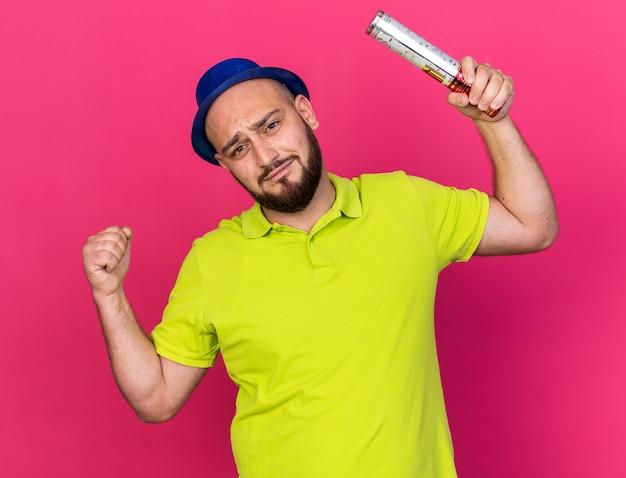 ピンクの壁に分離された強いジェスチャーを示す保持紙吹雪大砲を身に着けている緊張した若い男