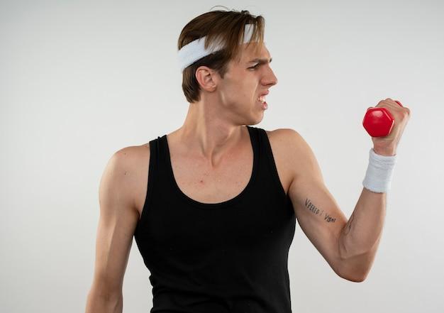 Teso giovane ragazzo sportivo che indossa la fascia e il braccialetto che si esercita con il manubrio isolato sul muro bianco