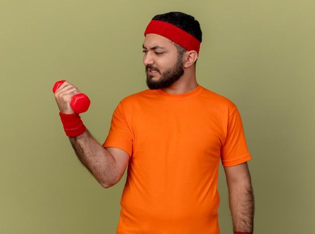 Напряженный молодой спортивный мужчина с повязкой на голову и браслетом, тренирующимся с гантелями, изолированными на оливково-зеленом фоне
