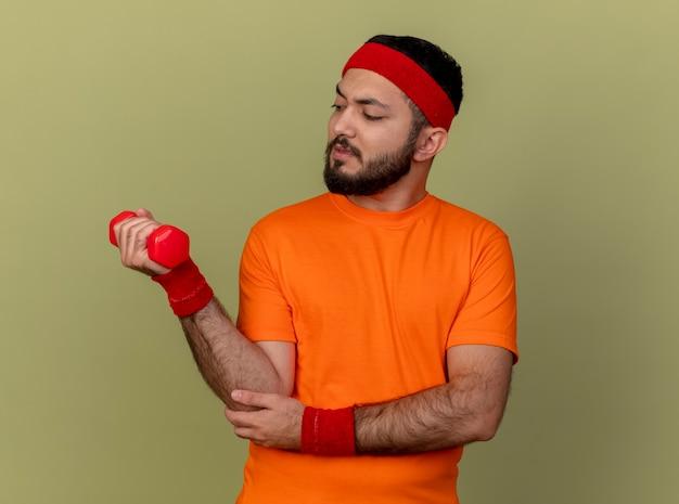 オリーブグリーンの背景に分離されたダンベルで運動するヘッドバンドとリストバンドを身に着けている緊張した若いスポーティな男
