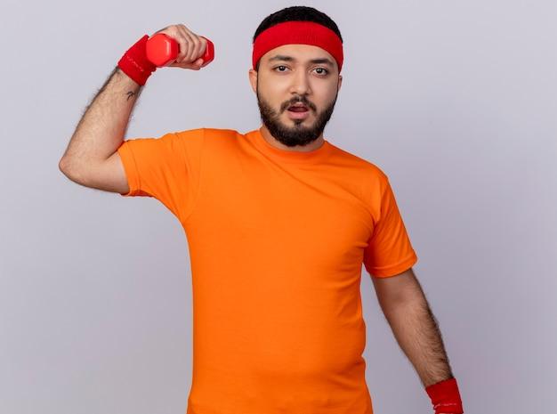 Напряженный молодой спортивный человек с повязкой на голову и браслетом, тренирующимся с гантелями, изолированными на белом фоне