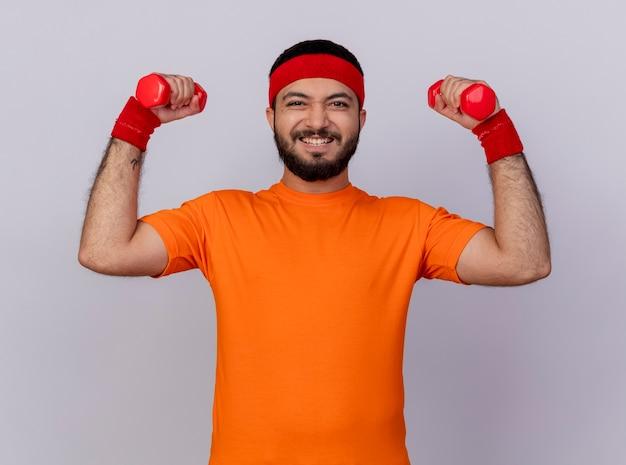Напряженный молодой спортивный мужчина с повязкой на голову и браслетом, тренирующимся с гантелями, изолированными на белом фоне