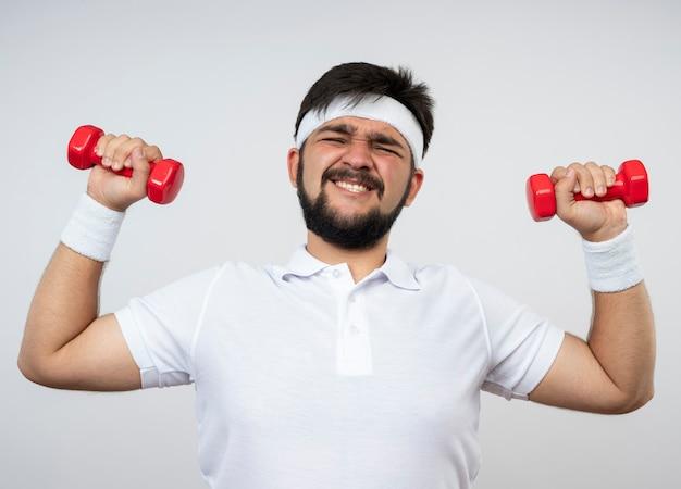 白い壁に分離されたダンベルで運動するヘッドバンドとリストバンドを身に着けている緊張した若いスポーティな男