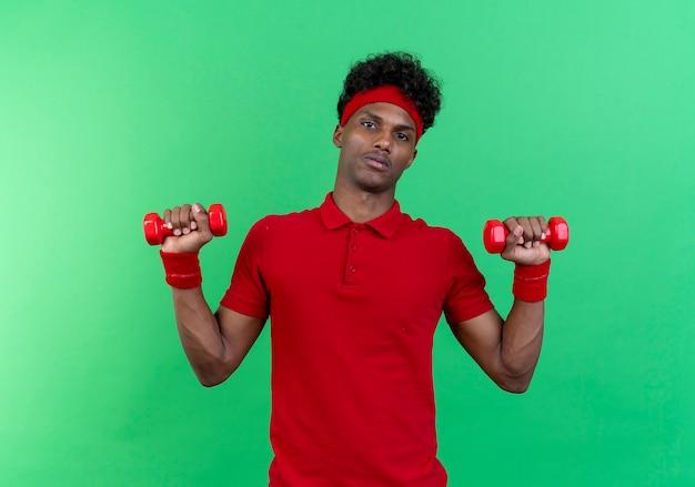 Напряженный молодой спортивный человек, носящий повязку на голову и упражнения на запястье