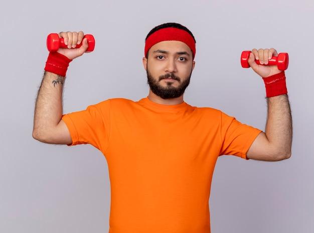 Напряженный молодой спортивный человек с повязкой на голову и браслет, поднимающий гантели, изолированные на белом фоне