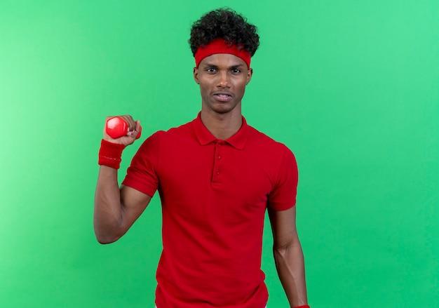 Напряженный молодой спортивный человек, носящий повязку на голову и браслет