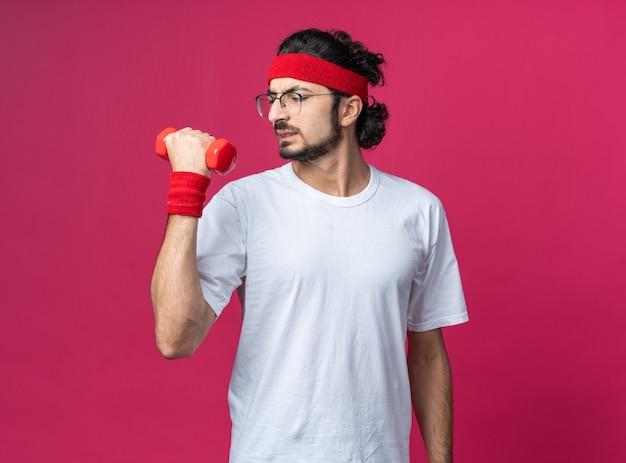 Напряженный молодой спортивный мужчина в головной повязке с браслетом и гантелями