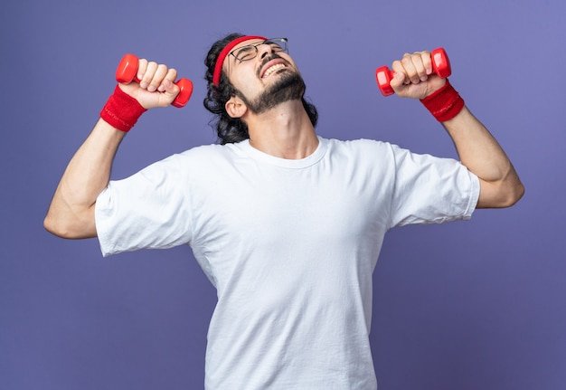 아령으로 운동하는 팔찌와 머리띠를 착용하는 긴장된 젊은 스포티 한 남자 프리미엄 사진