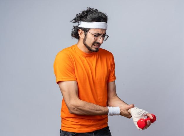 긴장된 젊은 스포티 한 남자는 아령으로 운동하는 붕대로 감긴 부상당한 손목과 손목 밴드와 함께 머리띠를 착용