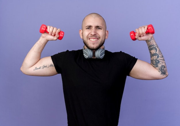 Напряженный молодой спортивный мужчина в наушниках тренируется с гантелями, изолированными на фиолетовом