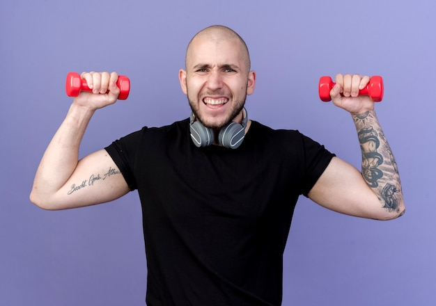 紫色で分離されたダンベルで運動している首にヘッドフォンを身に着けている緊張した若いスポーティな男