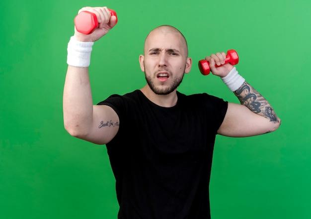 Напряженный молодой спортивный мужчина в браслете держит гантели и делает сильный жест, изолированный на зеленом