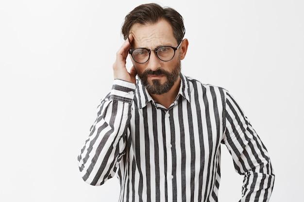 Напряженный и напряженный бородатый зрелый мужчина позирует