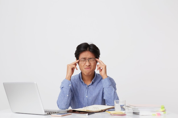 Tensed annoyed asian young business man in glasses sitting with eyes closed touching temples and feels stressed at the table over white wall