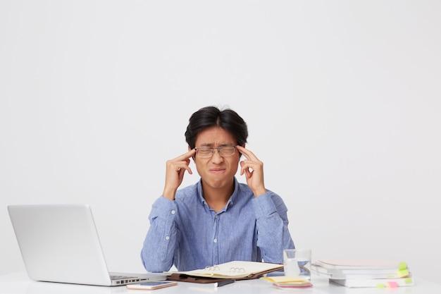 目を閉じてこめかみに触れて座って、白い壁の上のテーブルでストレスを感じる眼鏡をかけた緊張したイライラするアジアの若いビジネスマン