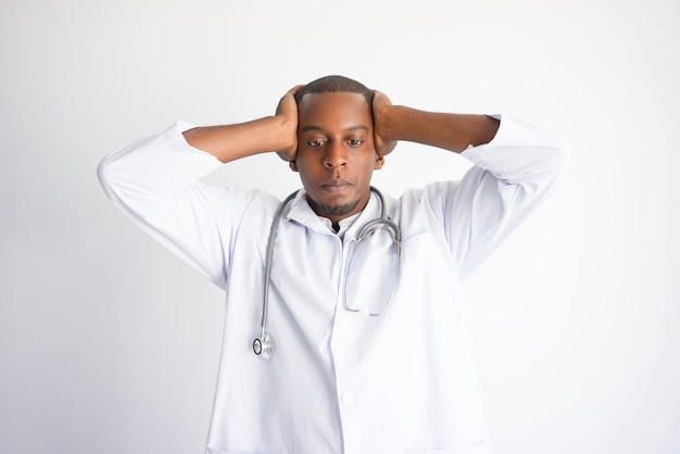 Tensed black male doctor clutching head. stressed doctor concept.