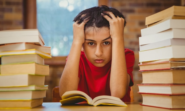 Tensed boy sitting with stack of books