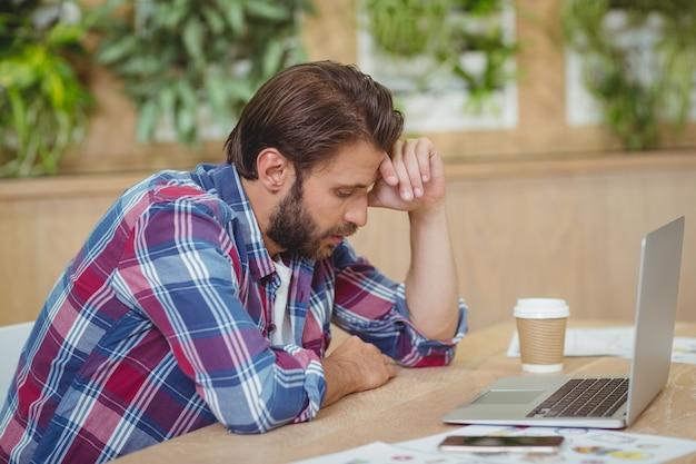 デスクに座っているラップトップを持つ緊張したビジネスエグゼクティブ