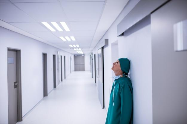 廊下の壁にもたれて緊張した女性外科医