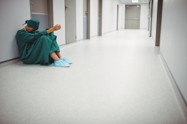 廊下に座っている緊張した女性外科医