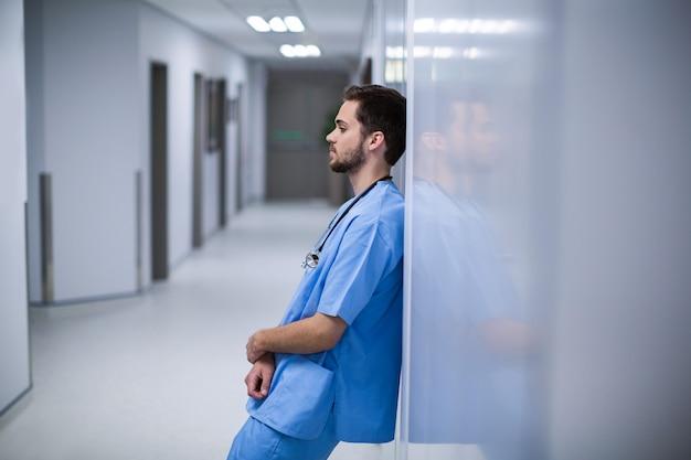 廊下の壁にもたれて緊張した男性看護師