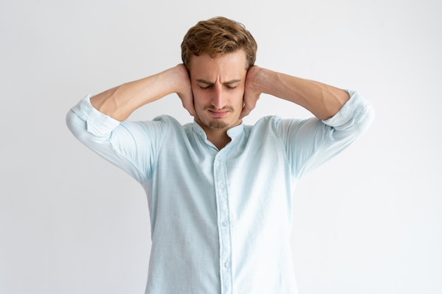 Tensed man covering ears with hands with his eyes closed