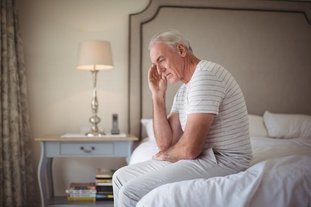 Напряженный мужчина сидит на кровати в спальне