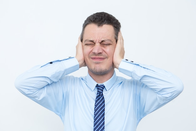 Tensed middle-aged business man covering ears