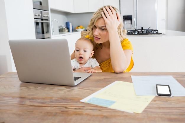 Tensed мать, используя ноутбук с ребенком мальчик в кухне