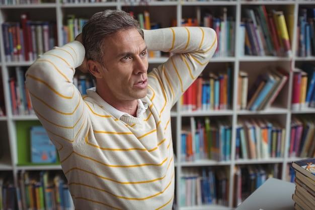 Напряженный школьный учитель сидит в библиотеке