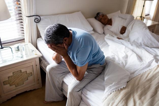 Напряженный старший мужчина сидит на кровати
