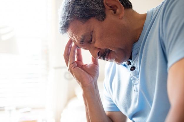 Напрягся старший мужчина сидит с рукой на лбу в спальне