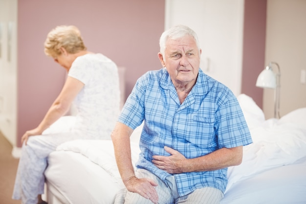 Tensed senior man and woman sitting on bed