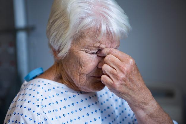 緊張したシニア患者が病院に立っています。