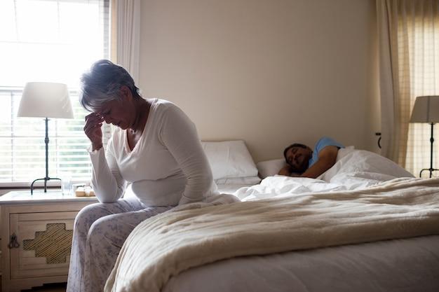 Напряженная старшая женщина сидит на кровати