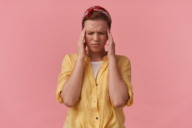 Tensed unhappy young woman in yellow shirt with headband on head and eyes closed touching her temples and having a headache over pink wall