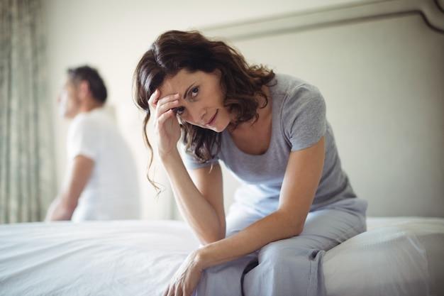 Напряженная женщина сидит на кровати