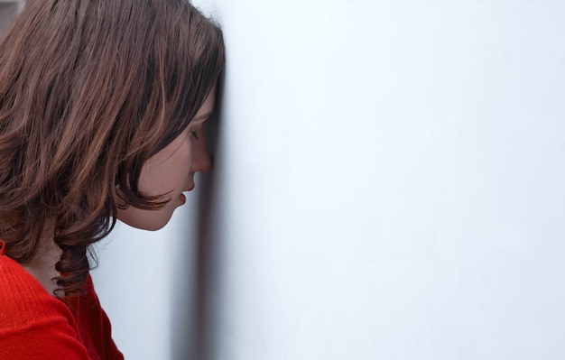 벽에 기대어 긴장된 젊은 여자