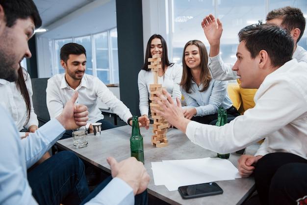 긴장이 공중에있다. 성공적인 거래를 축하합니다. 알코올로 테이블 근처에 앉아 젊은 직장인